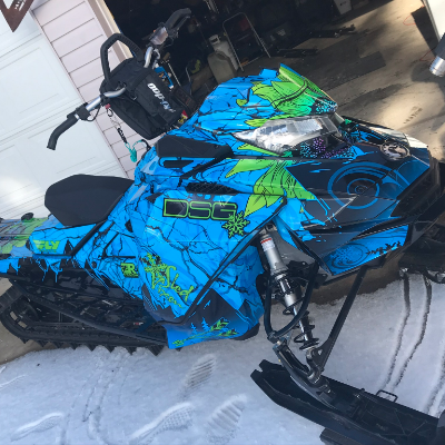 A striking blue and green snowmobile.