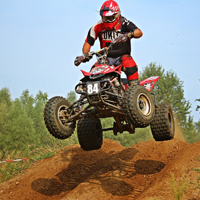 An ATV rider gets air over a dusty jump.