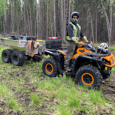 Travis Hallam rides his orange 2016 Can-Am Outlander XTP 1000 in the woods.