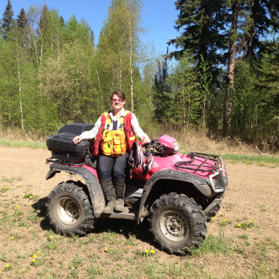 Trina Tosh wears a safety vest while sitting on a red ATV on a trail