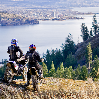 Motorcyclists look out at Kelowna from a high point