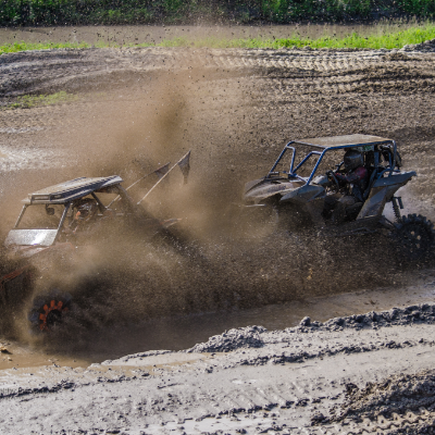 ATVs ride through the mud