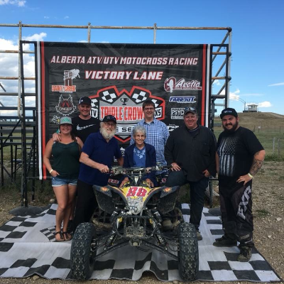 Jason Stapleton stands with friends with his ATV