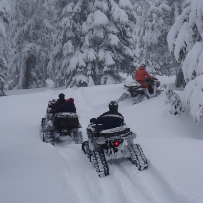 Three ATVs with tracks ride through the snow