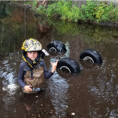 Taigen poses next to an overturned ATV