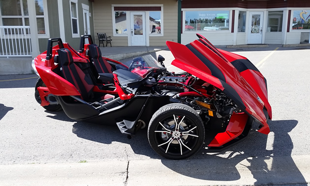 A shiny red Slingshot has the hood up for inspection.