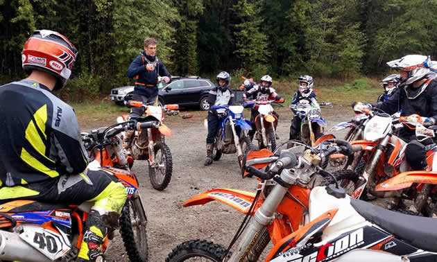 A group of dirt bike riders listening to Chris Birch.