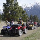 A group of ATVers lined up with mountains in background.