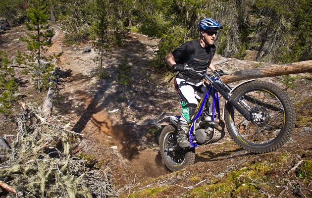 A man on a trials motorbike riding up a steep dirt bank.