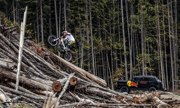 Sam King riding his trials bike on a slash pile.