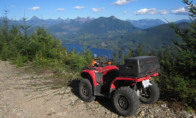 A red ATV parked on the side of a logging road overlooking Powell Lake.