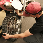 Dirt bike being checked for rear suspension issues.