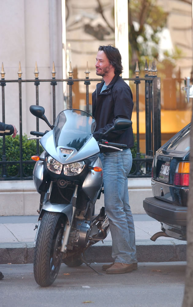 Keanu Reeves standing beside a sport bike.