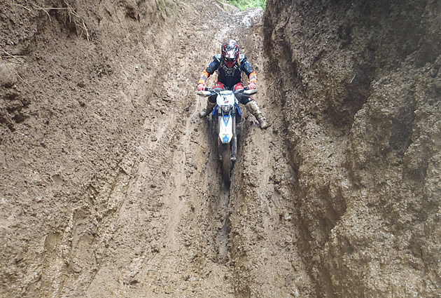 A motorcycle rider going through a deep groove in a muddy bank.
