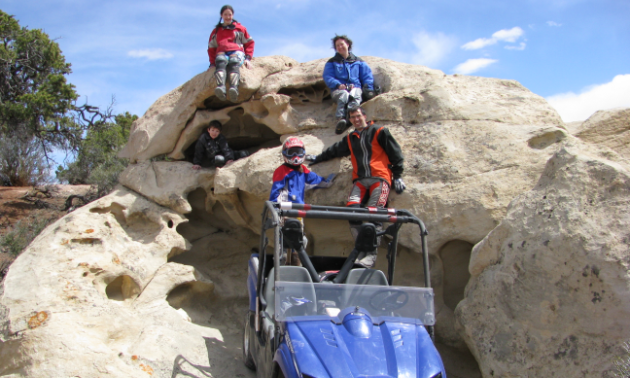 A family poses happily in front of a side-by-side on some large rocks in Richfield, Utah.