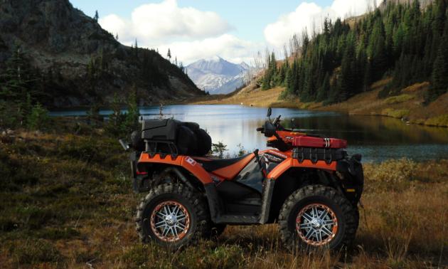 An ATV idles near a lake and mountains.