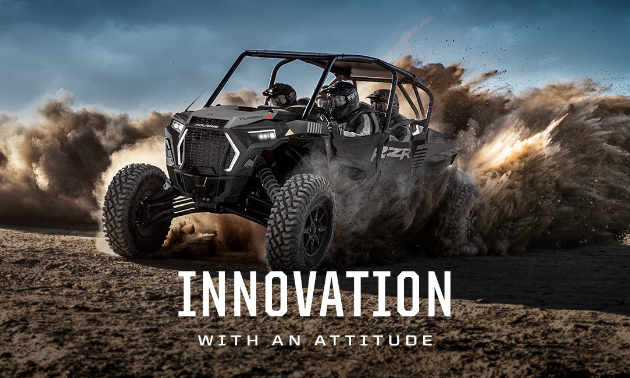 The new 2021 Polaris RZR drifts across the dirt.
