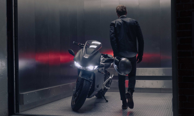 A man walks into a silver room and stands next to a Zero SR/S motorcycle with his back to the camera.