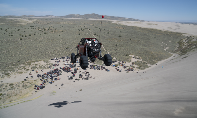 A UTV sails through the air over a steep decline on a sand dune. Many people and vehicles look like ants at the base of the hill.