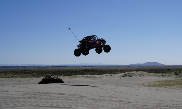 A UTV leaps up above the horizon from a dune in a desert.