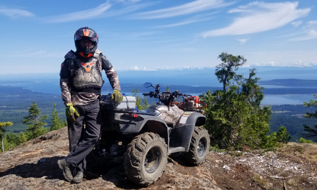 Al Ramey stands next to his 2013 Honda Rubicon on top of a mountain overlooking a valley.