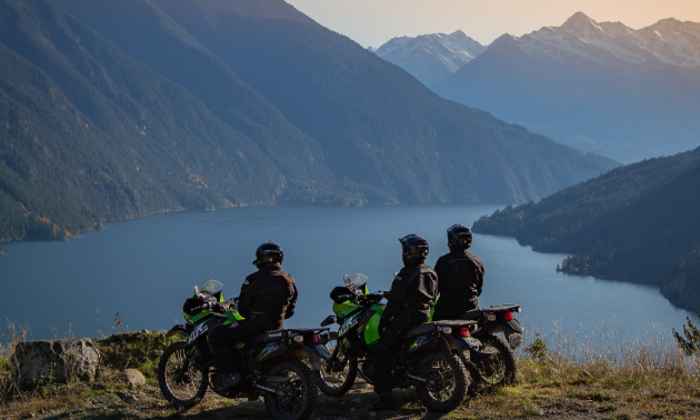 Motorcyclists stop and take in the view of Anderson Lake from up high on a mountain cliff.