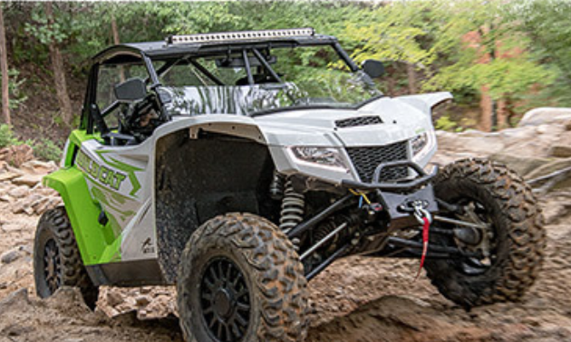 A 2021 Arctic Cat side-by-side climbs over rocky terrain.