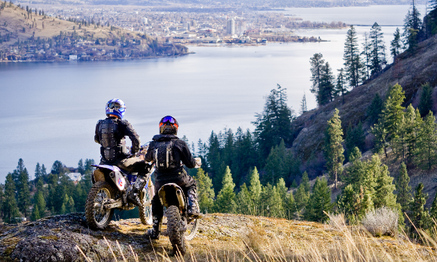 Two dirt bikers look over a river in a valley.