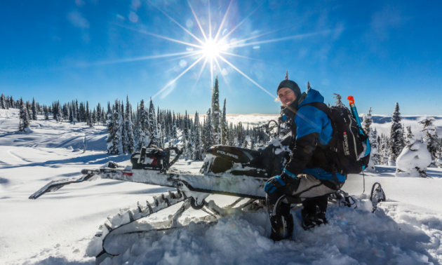 Billy Stevens smiles for the photo while leaning against his snowmobile in the snowy mountains.