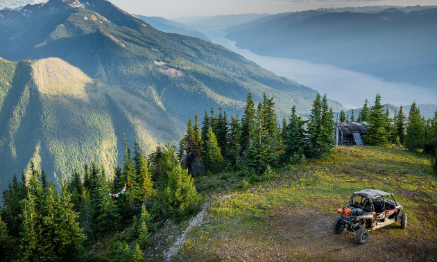 An ATV is parked on a green mountaintop. Another mountain and a river are in the background.