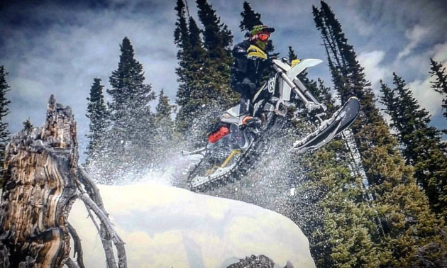 A white and black snow biker launches out over the camera for a wicked photo.