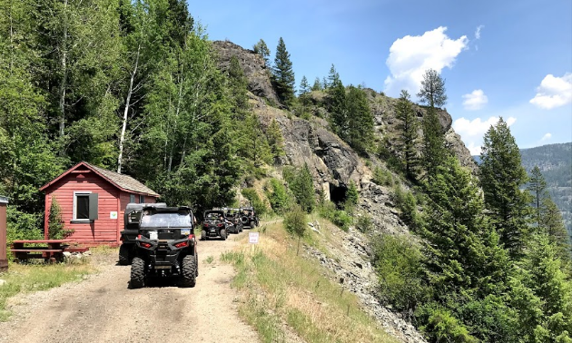 A row of ATVers ride along a trail on a mountainside.