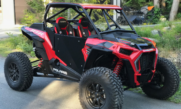A red UTV has a fashionable canopy and roll cage around its frame.