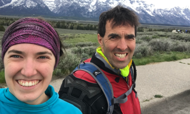 Marita Lindenbach and Graham Lindenbach smile in the foreground with mountains in the background.