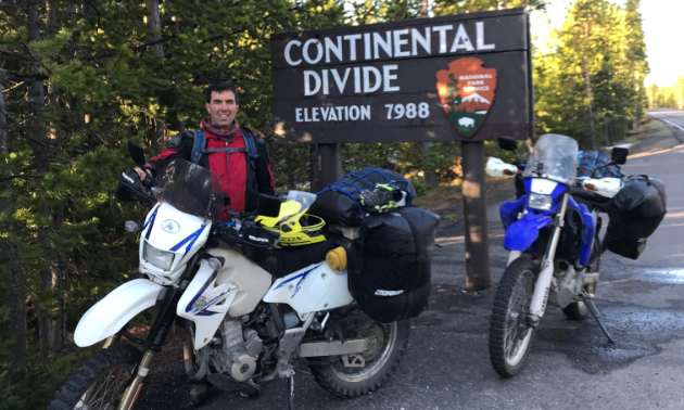Graham Lindenbach poses next to dirt bikes and a sign for the Continental Divide.