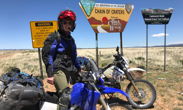 Marita Lindenbach stands on her dirt bike next to signs for the Continental Divide Trail in the desert.