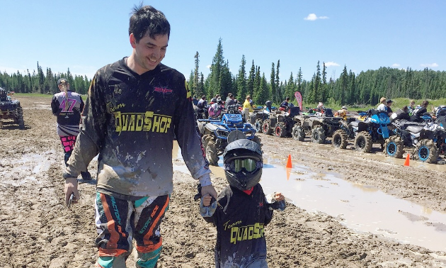 David Lawrence holds his son's hand as they walk near an ATV race track.