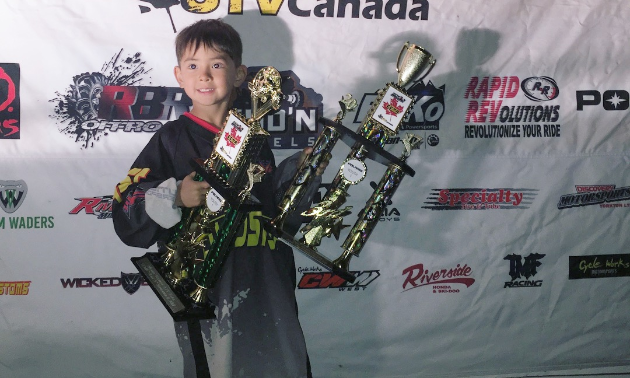 Aiden Lawrence poses with two giant trophies that nearly match him in size.