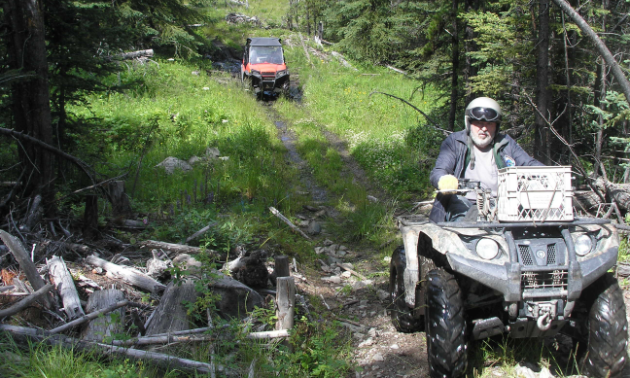 Bob Bogula rides a black ATV on Ridge Trail, followed by an orange UTV in the background.