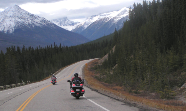 Motorcyclists ride down a road through the mountains.