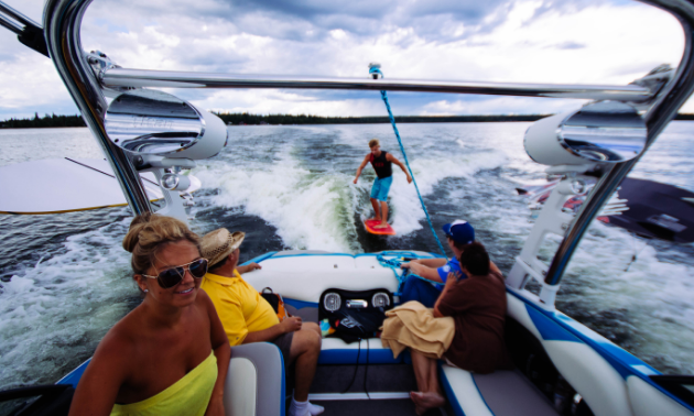 Happy people sit in a boat cruising across Waskesiu Lake with a wakeboarder trailing behind the boat.