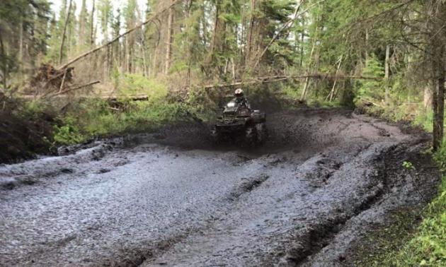 Ryan Ruf plows his ATV through a sludgy road.