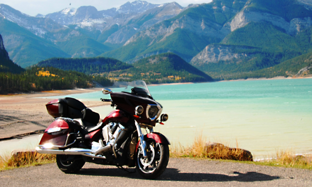 A maroon motorcycle shines in the sunshine in the foreground while a turquoise lake is in the background, followed by green, jagged mountains.
