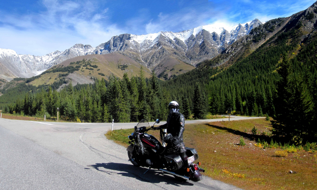 Don Morberg stands next to his motorcycle at the side of the road amidst towering mountains.