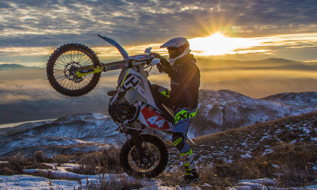 Dustin Labby does a wheelie while the sun breaks through the clouds behind him.