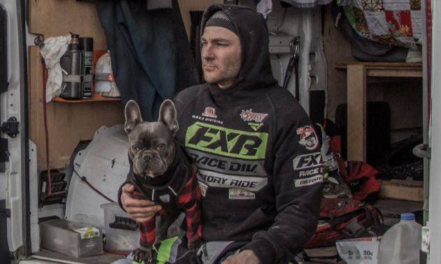 Dustin Labby sits on the end of a trailer with a dog on his lap.