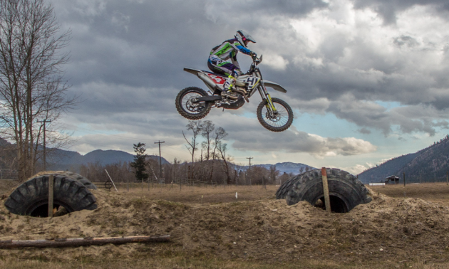 Dustin Labby gets big air as he jumps off of big tires in a field.