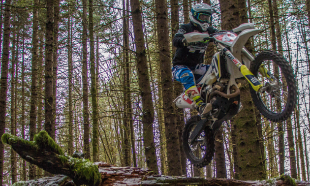 Dustin Labby leaps over a fallen tree on his motorbike.