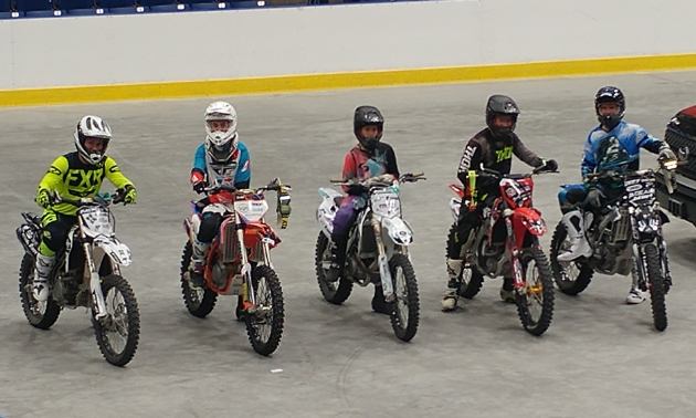 Five dirt bikers line up to take turns competing to be crowned champion.
