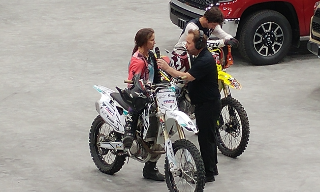 A man interviews Kassie Boone as she sits on her dirt bike.